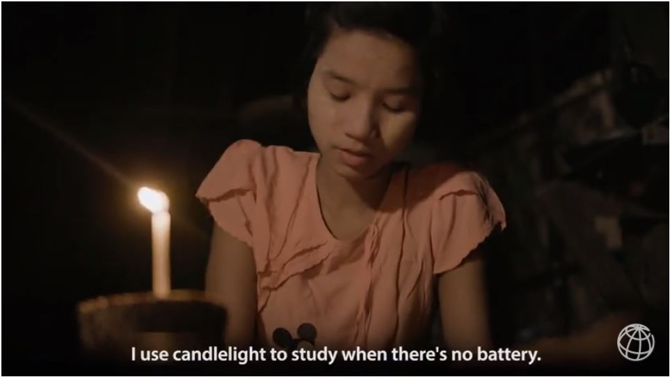 A young girl reads by candlelight in Myanmar