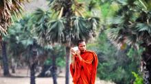 A Cambodian Monk listening to his cellphone. Photo by Amaryllis Liampoti